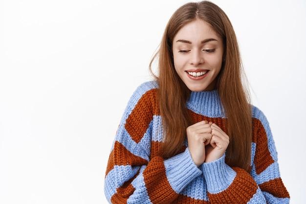 Mooie dwaze vrouw die lacht en naar beneden kijkt, verlegen of romantisch glimlacht, handen vasthoudt bij de borst, schattig staat tegen een witte muur
