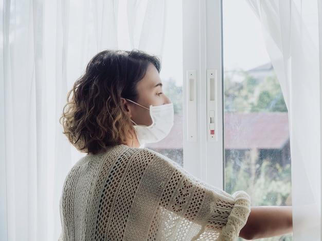 Mooie eenzame aziatische vrouw die medisch gezichtsmasker draagt dat uit het venster kijkt
