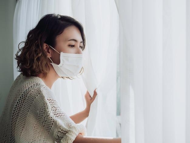 Mooie eenzame vrouw die medische gezichtsmasker draagt die uit het venster kijkt