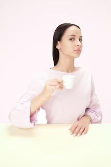 Mooie eenzame vrouw zit in roze studio en kijkt verdrietig met het kopje koffie in de hand. close-up afgezwakt portret in minimalistische stijl