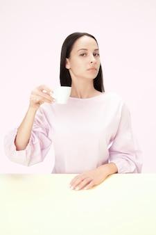 Mooie eenzame vrouw zit in roze studio en kijkt verdrietig met het kopje koffie in de hand.