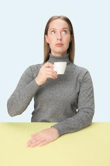 Mooie eenzame vrouw zit op blauwe studio en kijkt verdrietig met het kopje koffie in de hand.