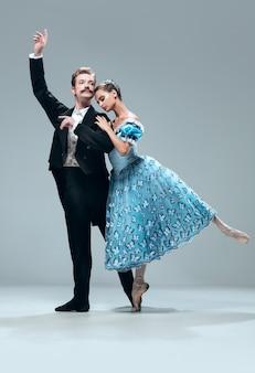 Mooie eigentijdse ballroomdansers die op grijze studiomuur worden geïsoleerd