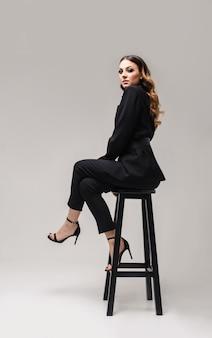 Mooie elegante bedrijfsvrouwenzitting op een stoel, op grijs