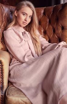 Mooie elegante blondevrouw in roze kledingszitting in leerleunstoel