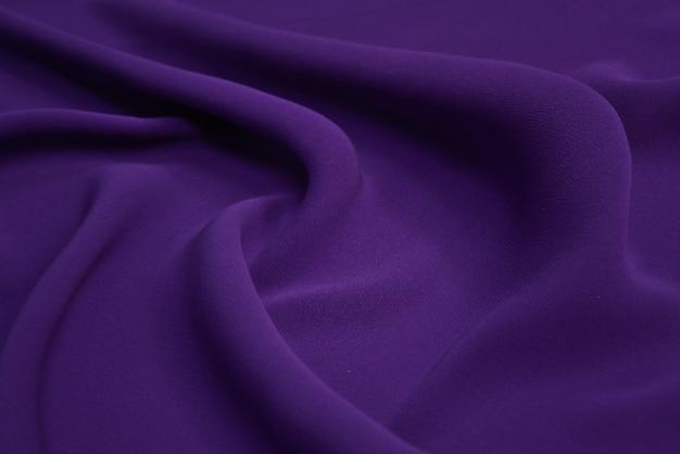 Mooie elegante golvende violet paars satijn zijde luxe doek stof textuur met violette achtergrond