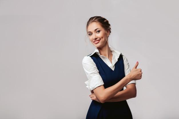 Mooie elegante jonge bussinesvrouw die zich op de studio met grijze achtergrond bevinden