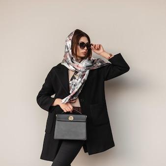 Mooie elegante jonge vrouw in luxe zijden sjaal op hoofd in zwarte stijlvolle jas met trendy lederen handtas rechtzetten vintage zonnebril in de buurt van muur binnenshuis. chique moderne professionele meisjesmannequin.