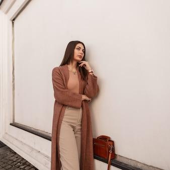Mooie elegante jonge vrouw in modieuze jas in broek met lederen stijlvolle bruine handtas staat in de buurt van witte muur op straat. sexy stedelijke aantrekkelijk meisje vormt in de stad. lente casual trendy outfit.