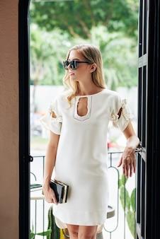 Mooie elegante jonge vrouw permanent in café ingang en wegkijken