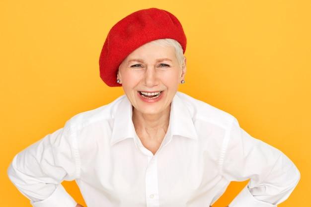 Mooie elegante volwassen europese vrouw, gekleed in wit overhemd en rode hoed openen mond