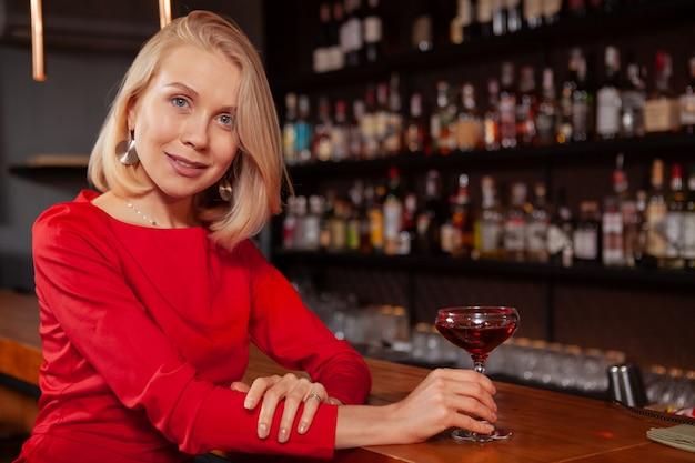 Mooie elegante vrouw die in rode kleding aan de camera glimlacht, genietend van haar cocktail bij lokale bar