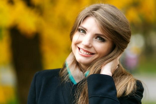 Mooie elegante vrouw die zich in een park in de herfst bevindt