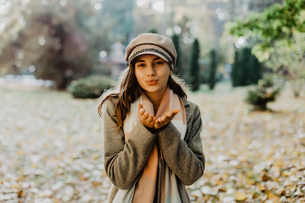 Mooie elegante vrouw die zich in park in de herfst bevindt