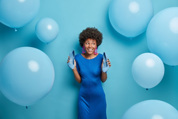 Mooie elegante vrouw in blauwe jurk, houdt hoge hak schoenen, geniet van feest, heeft plezier op feestje, kijkt met een glimlach opzij, poseert rond ballonnen. afro-amerikaanse dame draagt modieuze outfit