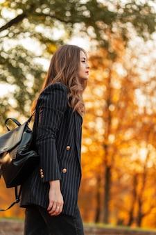 Mooie elegante vrouw in modieus zwart pak met stijlvolle blazer en leren rugzak loopt in het park met gekleurd geel herfstgebladerte bij zonsondergang