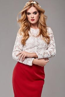 Mooie elegante vrouw in modieuze rode en witte jurk