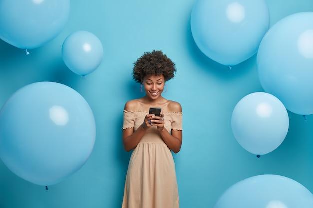 Mooie elegante vrouw kijkt vrolijk naar smartphoneapparaat, lacht aangenaam en leest goed nieuws op internet, gekleed in lange zomerjurk, poseert tegen blauwe muur versierd met ballonnen