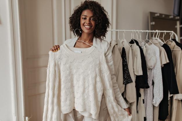 Mooie elegante vrouw met een donkere huid in een beige jas lacht, kijkt naar voren en houdt hanger met witte gebreide trui vast