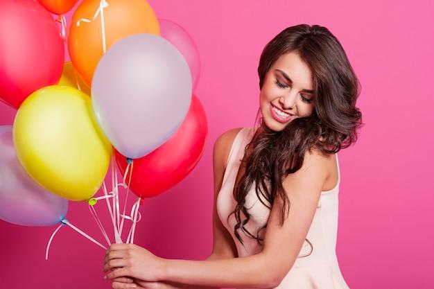 Mooie elegante vrouw met multi gekleurde ballonnen