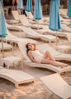 Mooie elegante vrouw ontspannen op het strand van hotel resort
