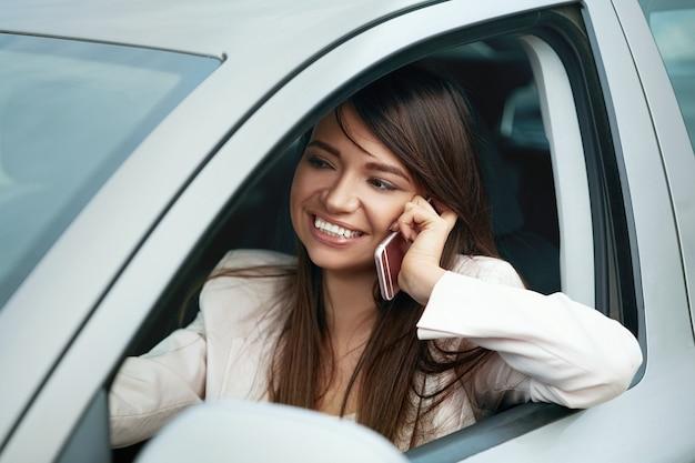 Mooie elegante vrouw praten aan de telefoon tijdens het reizen met de auto