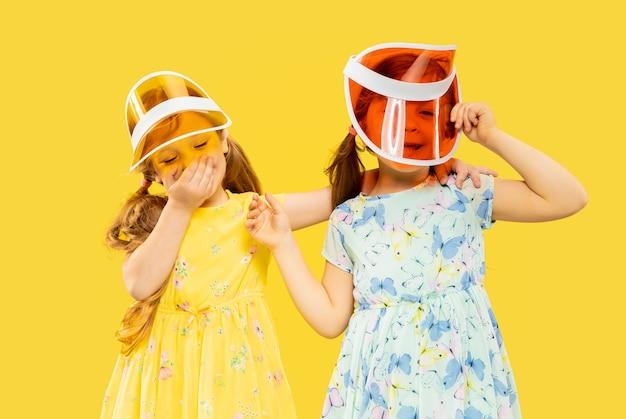 Mooie emotionele kleine meisjes die op geel worden geïsoleerd