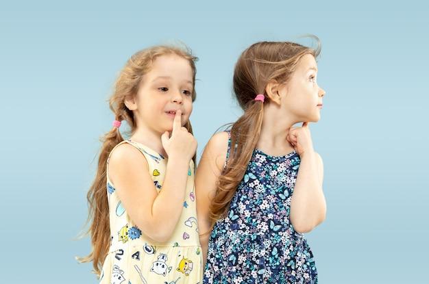 Mooie emotionele kleine meisjes geïsoleerd op blauw