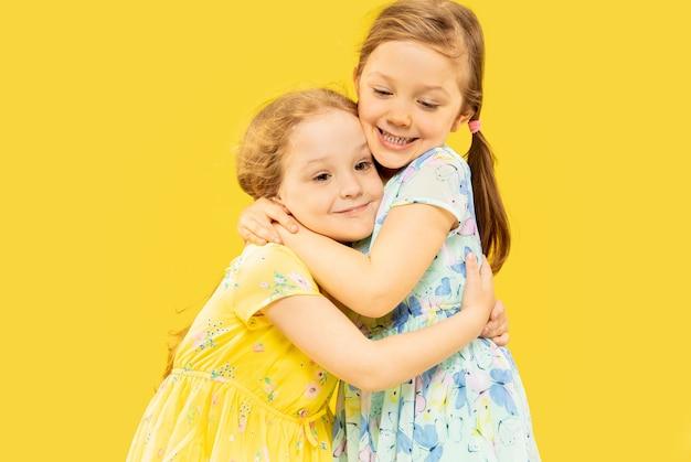 Mooie emotionele kleine meisjes geïsoleerd op gele ruimte. halflang portret van twee gelukkige zusters die jurken dragen en elkaar omhelzen