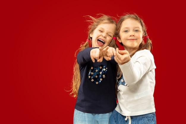 Mooie emotionele kleine meisjes geïsoleerd op rode studio
