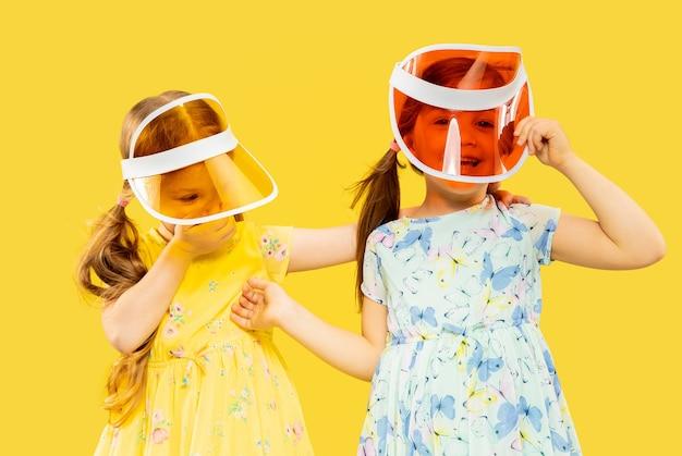 Mooie emotionele kleine meisjes geïsoleerd. portret van twee zussen vol geluk die jurken en petten dragen. concept van de zomer, menselijke emoties, kindertijd.