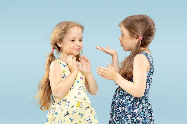Mooie emotionele kleine meisjes op blauw