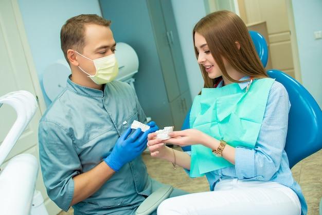 Mooie emotionele meisjeszitting als tandvoorzitter naast een mannelijke arts. tandarts. arts en patiënt