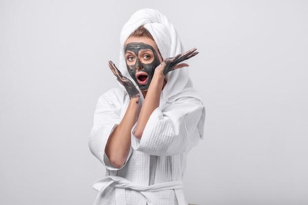 Mooie emotionele model poseren in een witte badjas met een handdoek op haar hoofd