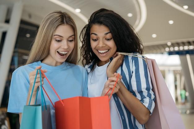 Mooie emotionele vrouwen die boodschappentassen in winkelcentrum houden. groot verkoopconcept