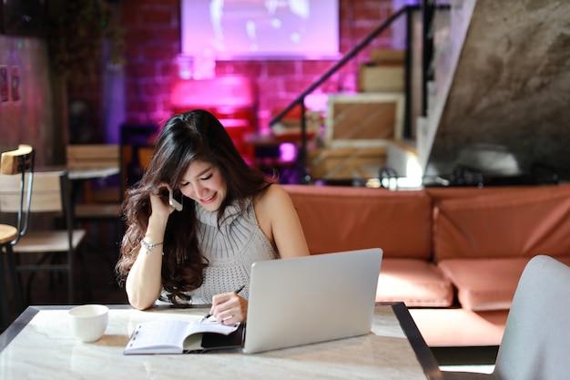 Mooie en aantrekkelijke aziatische vrouw, lang haar in grijze casual kleding werken