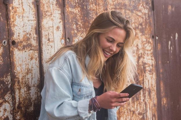 Mooie en aantrekkelijke vrouwentiener die haar telefoon alleen in een stad met stedelijke muur op de achtergrond gebruikt - blonde dame die aan het chatten is of iets grappigs kijkt