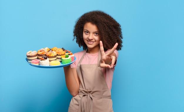 Mooie en afro-tiener die vriendelijk glimlacht kijkt, nummer twee of seconde met vooruit hand toont, aftellend. humoristisch bakkersconcept