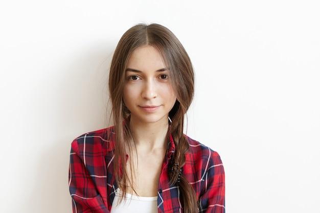 Mooie en charmante jonge blanke vrouw met bruine ogen en slordig donker haar