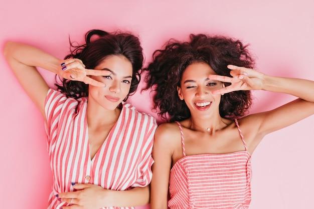 Mooie en charmante meisjes in schattige roze pyjama's liggen op hun rug en tonen twee vingers ter ondersteuning van de wereldvrede.