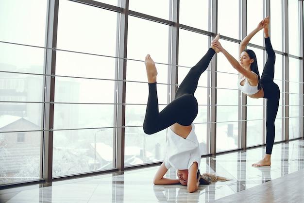 Mooie en elegante meisjes die yoga doen