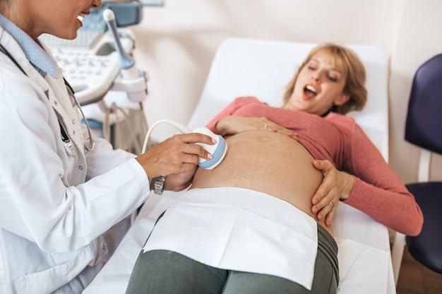 Mooie en gelukkige aanstaande moeder bij gynaecologisch onderzoek met echografie medische apparatuur.