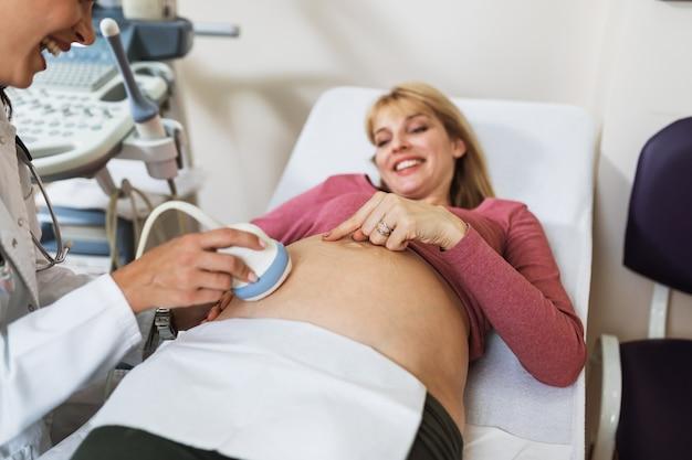 Mooie en gelukkige aanstaande moeder die echografie doet in de prenatale kliniek.
