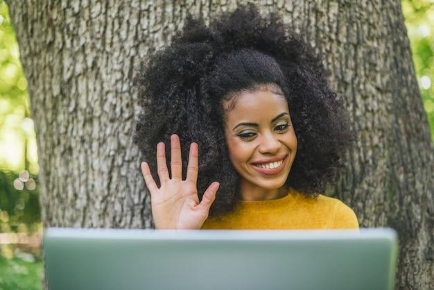 Mooie en gelukkige afrovrouw die op videogesprek met laptop in een tuin spreekt. selectieve aandacht.