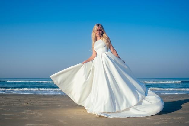 Mooie en gelukkige bruid in een chique lange witte trouwjurk dwarrelt en danst op het strand. trouwjurk evolueert en vliegt tijdens een dans op het strand