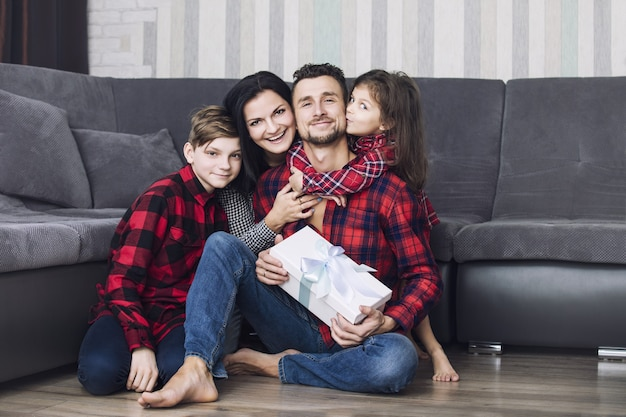 Mooie en gelukkige familie geeft een geschenk aan de vader bij de gelegenheid samen thuis in de woonkamer