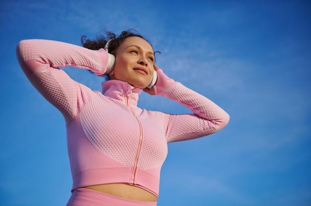 Mooie en gelukkige gemengde rasvrouw in roze sportkleding in hoofdtelefoons die van muziek op een blauwe heldere hemelachtergrond genieten
