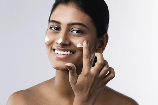Mooie en gelukkige indiase vrouw vochtinbrengende crème op haar gezicht toe te passen
