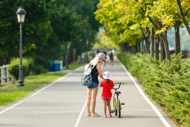 Mooie en gelukkige jonge moeder die haar leuke dochter onderwijzen om een fiets te berijden