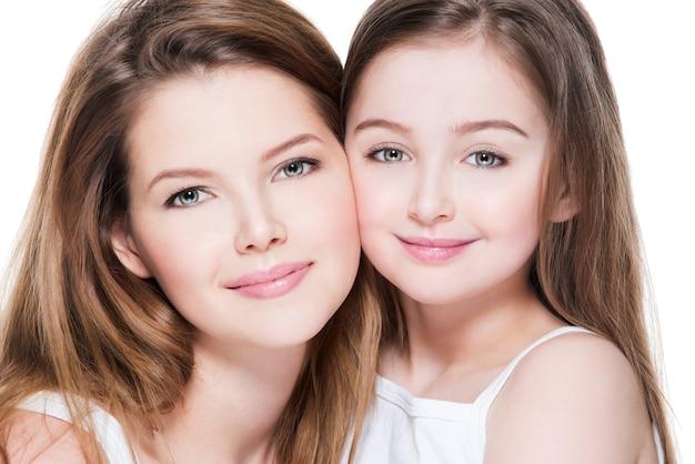 Mooie en gelukkige jonge moeder met een kleine dochter 8 jaar omhelzen elkaar in de studio